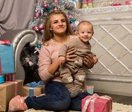 Happy mother with newborn son, sitting on a floor near a Christmas tree. Waiting for a holiday. Royalty Free Stock Photography