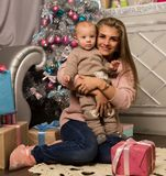 Happy mother with newborn son, sitting on a floor near a Christmas tree. Waiting for a holiday. Family values concept Stock Photos