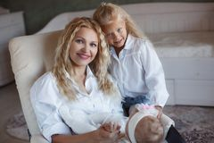 Happy mother with older and little daughter at home stock images