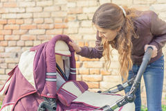 Happy mother at outdoor shakes a baby carriage. Happy mother at outdoor wearing a spring jacket shakes a baby carriage Stock Image
