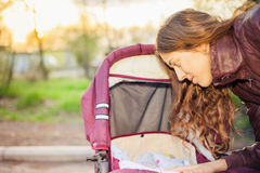 Happy mother at outdoor shakes a baby carriage Stock Image