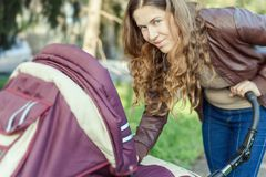 Happy mother at outdoor shakes a baby carriage. Happy mother at outdoor wearing a spring jacket shakes a baby carriage Royalty Free Stock Photo