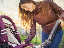 Happy mother at outdoor shakes a baby carriage. Happy mother at outdoor wearing a spring jacket shakes a baby carriage Royalty Free Stock Photography