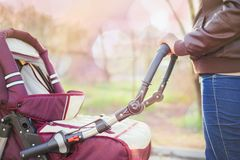 Happy mother at outdoor shakes a baby carriage Royalty Free Stock Photos