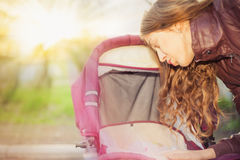 Happy mother at outdoor shakes a baby carriage. Happy mother at outdoor wearing a spring jacket shakes a baby carriage with copy space for any text at sunlight Royalty Free Stock Photography