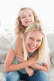 Happy mother piggybacking daughter on sofa stock photo