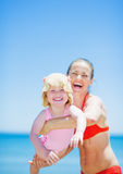 Happy mother playing with baby on beach Stock Images