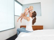Happy mother playing with baby in bedroom Stock Photos
