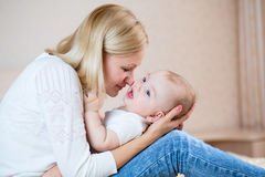 Happy mother playing with baby boy indoors Stock Photography