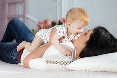 Happy mother playing with baby boy lying on bed at home. Funny kid with red hair and blue eyes,dressed in a white t-shirt with grey stars and plays on the bed in Royalty Free Stock Photos