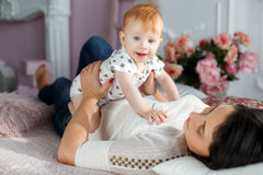Happy mother playing with baby boy lying on bed at home. Funny kid with red hair and blue eyes,dressed in a white t-shirt with grey stars and plays on the bed in Stock Photo