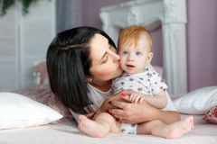 Happy mother playing with baby boy lying on bed at home. Funny kid with red hair and blue eyes,dressed in a white t-shirt with grey stars and plays on the bed in Royalty Free Stock Images
