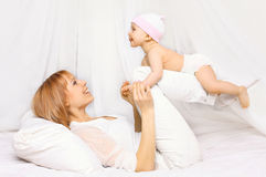 Happy mother playing with baby having fun together on the bed royalty free stock photos