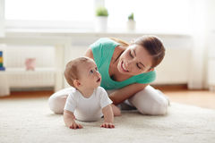 Happy mother playing with baby at home Stock Photos