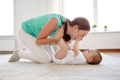 Happy mother playing with baby at home Stock Images