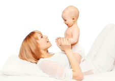 Happy mother playing with baby lying over white Stock Images
