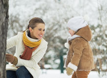 Happy mother playing with baby in winter park Stock Images
