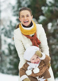 Happy mother playing with baby in winter park Royalty Free Stock Image