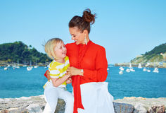 Happy mother playing with child in front of lagoon with yachts Stock Photo