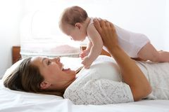Happy mother playing with cute baby in bed Royalty Free Stock Photography
