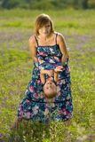 Happy mother playing with daughter in field. Outdoor shot Stock Photography