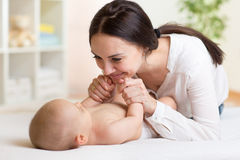 Happy mother playing with her baby in bedroom Stock Photos