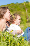 Happy mother playing with her child girl outdoors Stock Photos