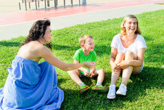 Happy mother playing with her children. Tickling her daughter and near smilling son stock images