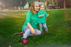 Happy mother playing with her daughter on the grass. In the park Royalty Free Stock Image