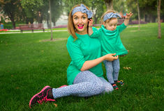 Happy mother playing with her daughter on the grass. In the park Royalty Free Stock Images