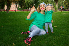 Happy mother playing with her daughter on the grass. In the park Royalty Free Stock Photography