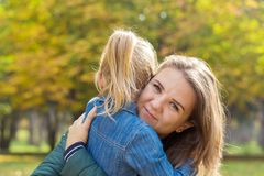 Happy mother playing with her daughter hugging her in the park royalty free stock photo
