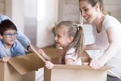 Happy mother playing with kids unpacking boxes at new house stock photos