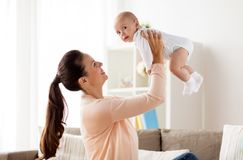 Happy mother playing with little baby boy at home stock image