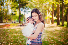 Happy mother playing with little daughter in autumn park Stock Photography