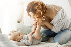 Happy mother playing with newborn baby kissing little legs spending best maternity moments in cozy bedroom. Warm family