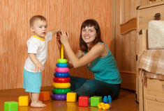 Happy mother plays with baby Stock Images