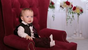 Happy mother plays with beloved little son at home sitting in a soft chair. A little one-year-old boy in a shirt with a bow tie sits in a chair. Portrait stock video footage