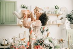 Happy mother plays and kisses her baby in the kitchen royalty free stock photography
