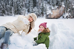Happy mother pointing in camera to child while playing outdoors Stock Image