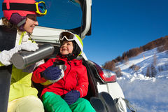 Happy mother pouring tea for her son after skiing Royalty Free Stock Photos
