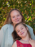 Happy mother and pre-teen daughter. Standing together outside under a tree Royalty Free Stock Image