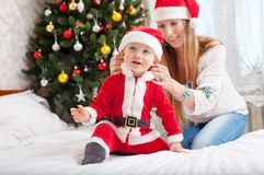 Happy mother putting Santa costume on toddler son Stock Image