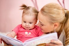 Happy mother read a book to baby girl Stock Photo