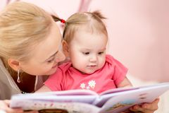 Happy mother read book to baby girl indoors Stock Photos