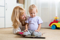 Happy mother read a book to child boy indoors Stock Photo