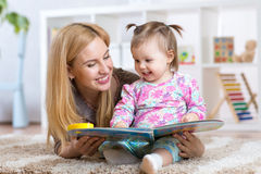 Happy mother read a book to child girl indoors Stock Photo