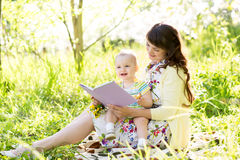 Happy mother reading baby outdoors Royalty Free Stock Photos