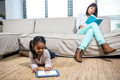 Happy mother reading book while her daughter using tablet Royalty Free Stock Photos