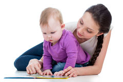 Happy mother reading a book to baby girl Stock Photo